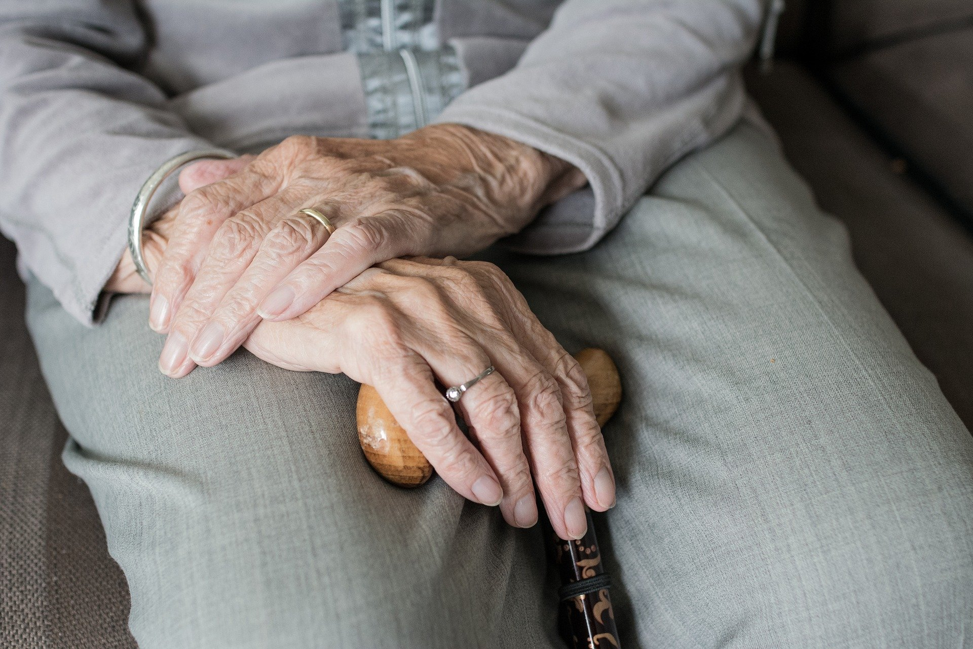 na zdjęciu siedząca starsza osoba z laską
