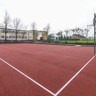 widok na boisko do gry w koszykówkę w Szkole Podstawowej w Terespolu Pomorskim, w tle szkoła