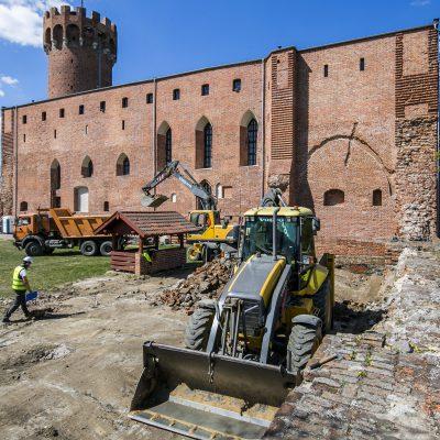 widok na maszyny budowlane, w tle zamek krzyżacki w Świeciu