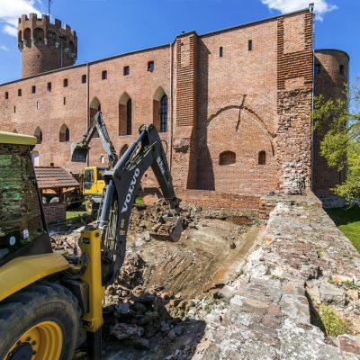 widok na pracujące koparki, w tle zamek krzyżacki w Świeciu