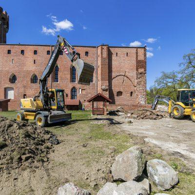 remont zamku krzyżackiego, na pierwszym planie koparki, w tle zamek krzyżacki