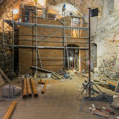 rusztowania we wnętrzu remontowanego zamku krzyżackiego, na pierwszym planie lampa oraz rury kanalizacyjne