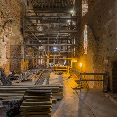 rusztowania we wnętrzu remontowanego zamku krzyżackiego, widok na wprost, na pierwszym planie deski i druty zbrojeniowe