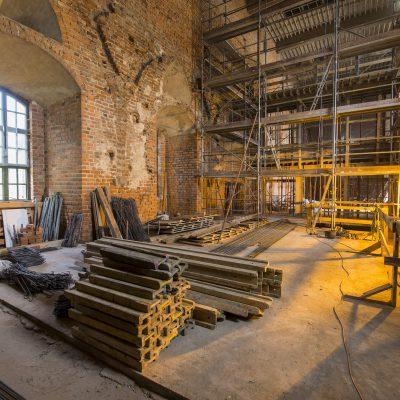 rusztowania we wnętrzu remontowanego zamku krzyżackiego, na pierwszym planie deski i druty zbrojeniowe