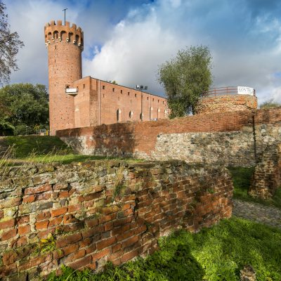 widok na zniszczony mur obronny zamku, w tle zamek krzyżacki w Świeciu
