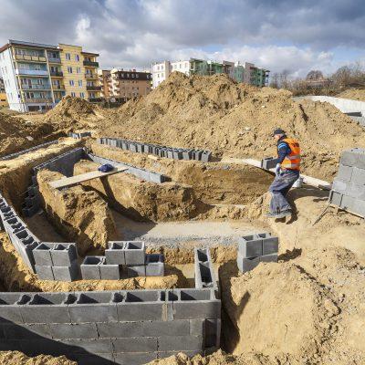 widok na budowę Art- Parku, robotnik prznoszący cegły