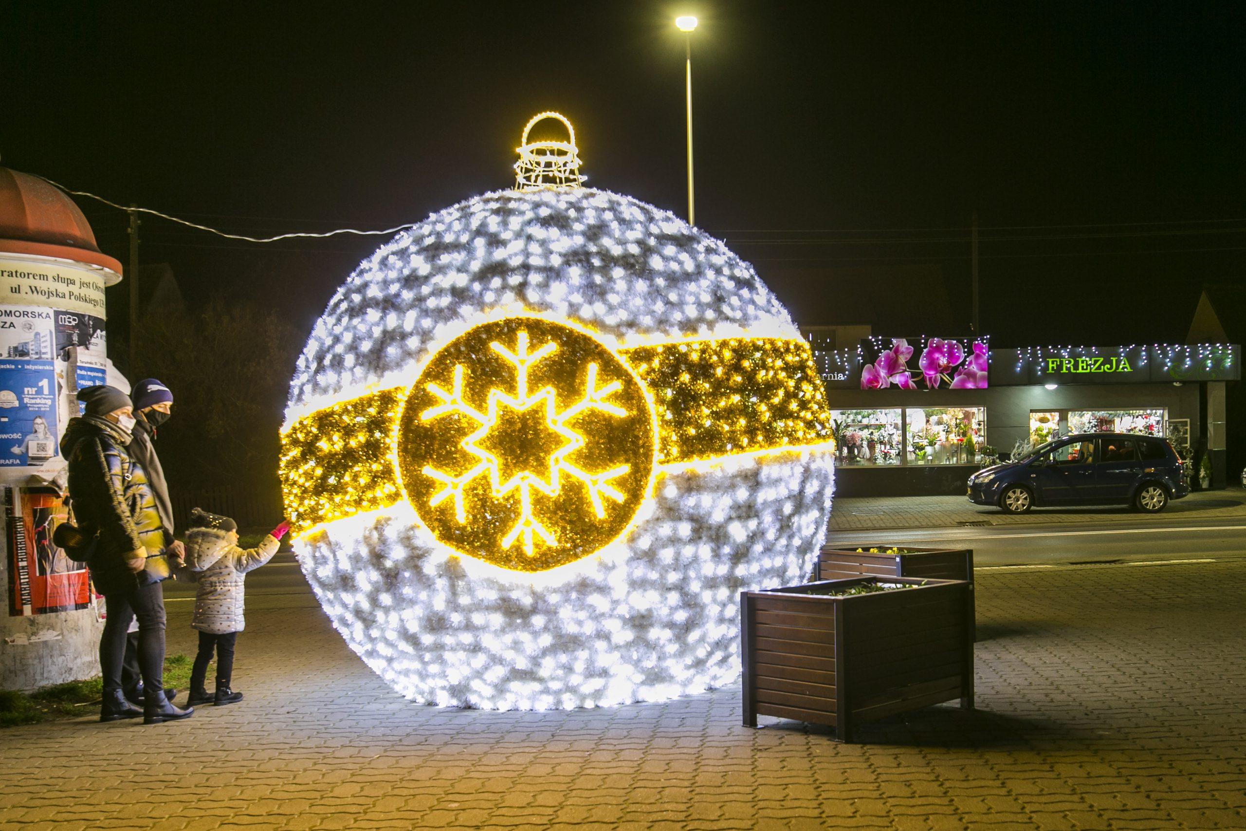 rozświetlona bombka świąteczna dużych rozmiarów, obok rodzina z dzieckiem