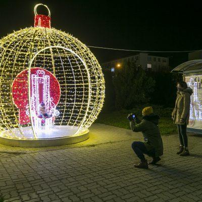widok na świecącą ozdobę świąteczną, bombkę z krzesłem w środku, na krześle dziecko pozujące do zdjęcia, na pierwszym planie osoba wykonująca zdjęcie