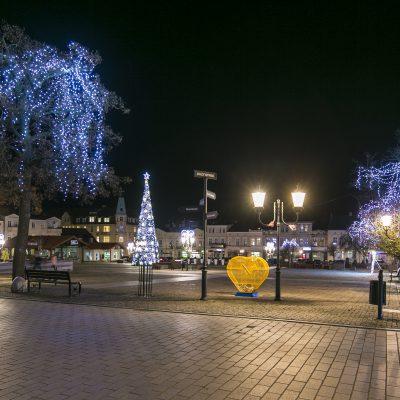 nocny widok na Duży Rynek w Świeciu od strony Urzędu Stanu Cywilnego, na pierwszym planie drzewa ustrojone świecącymi ozdobami, w tle choinkia świąteczna