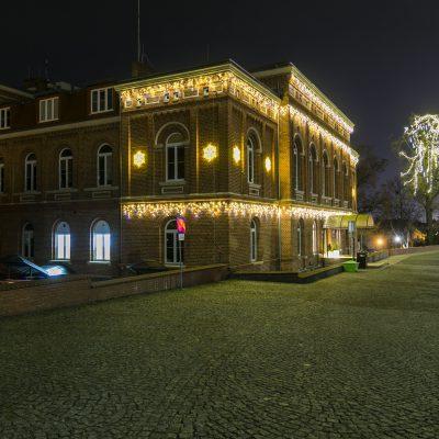 nocny widok na Urząd Miejski w Świeciu, na budynku świecące ozdoby świąteczne, w tle drzewo przystrojone świecącymi ozdobami świątecznymi