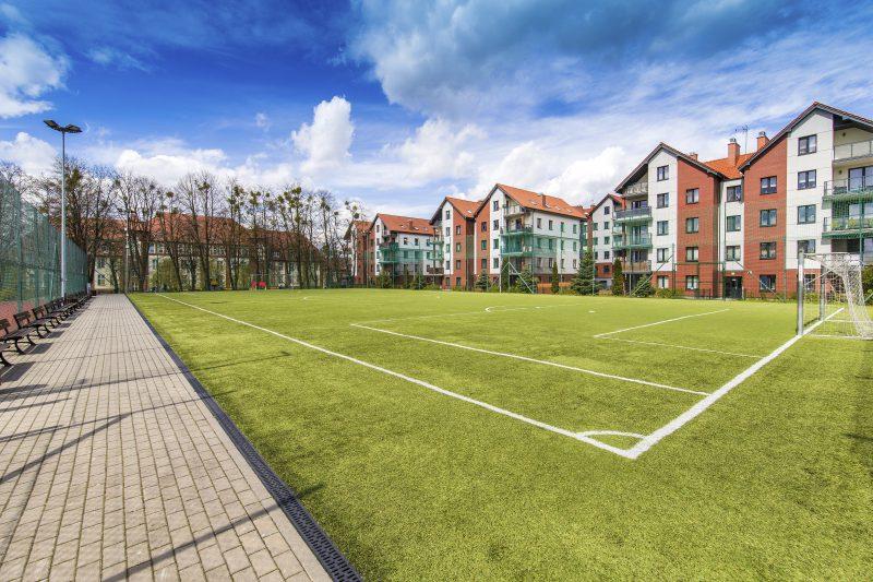 widok na murawę boiska, w oddali bloki mieszkalne