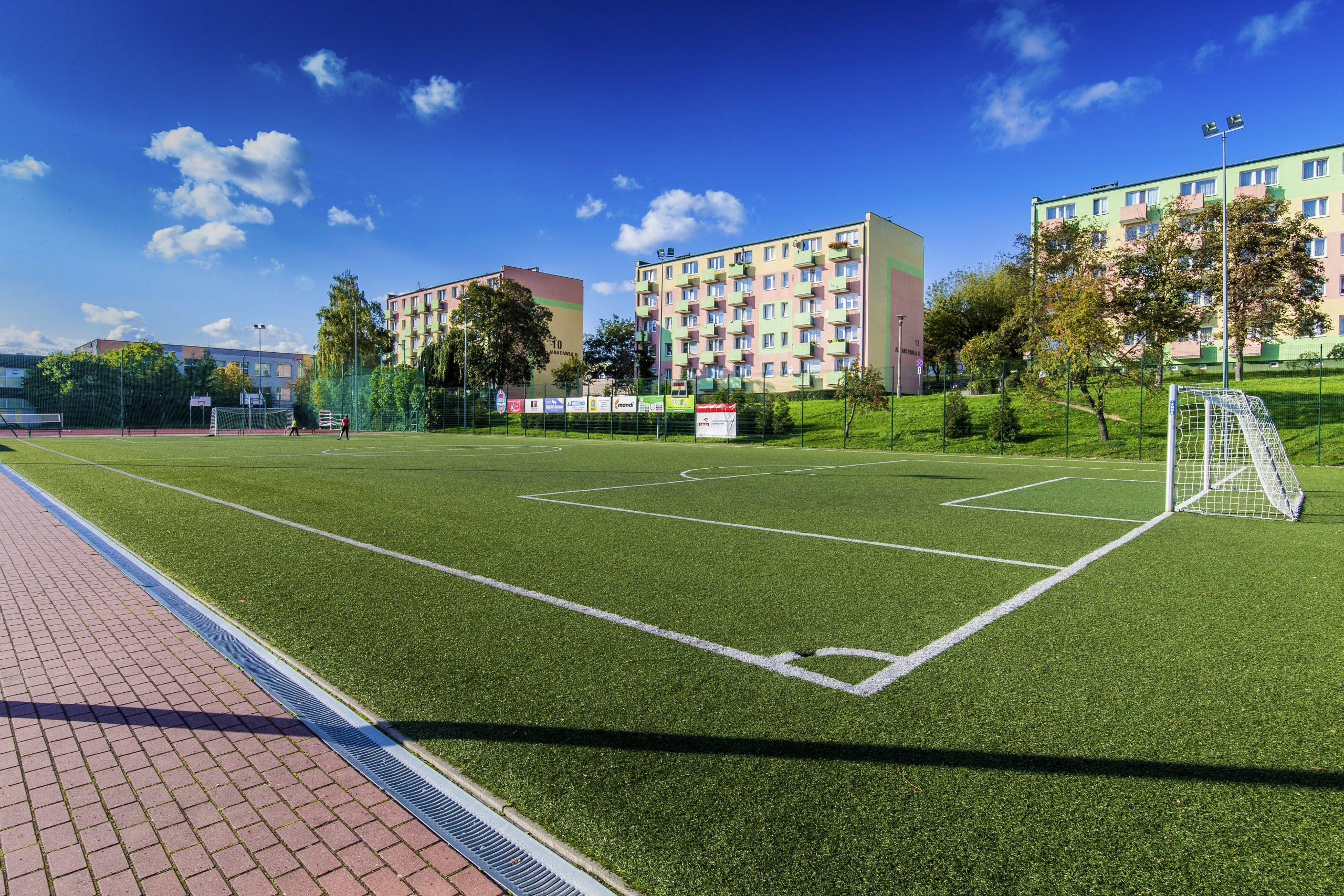 widok na sztuczną murawę boiska, w tle bloki mieszkalne