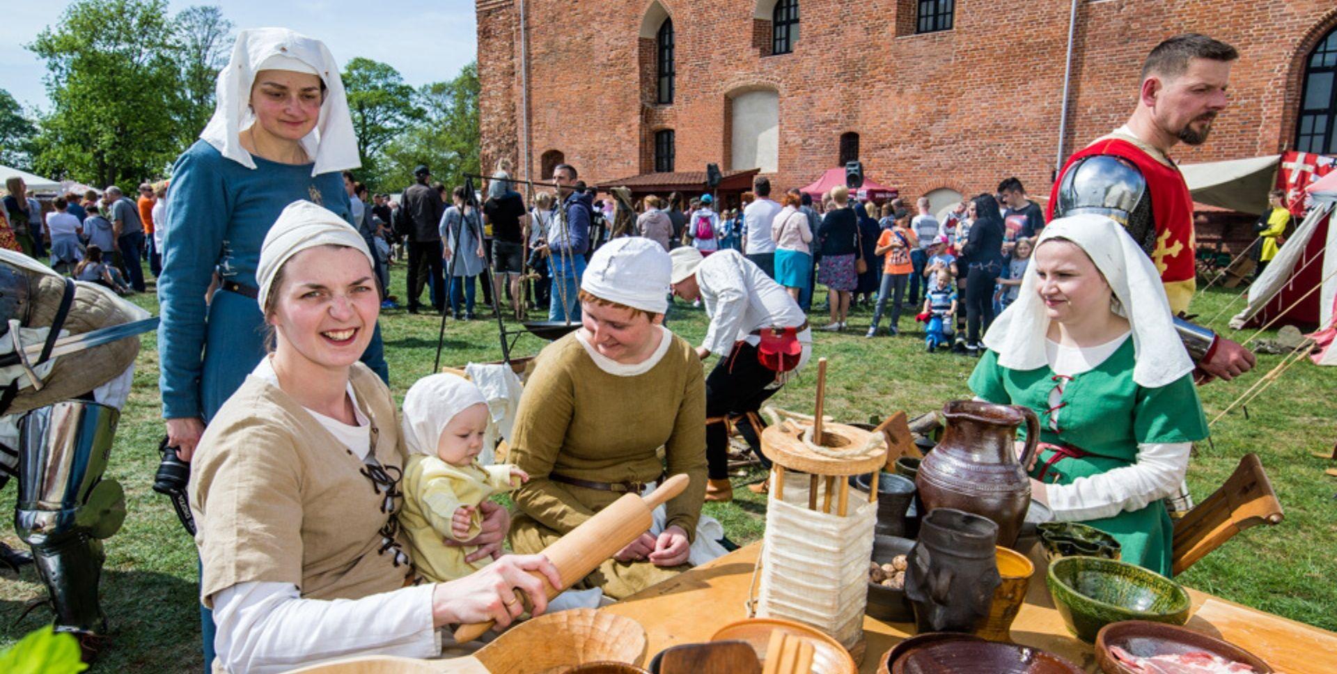 Osoby w strojach historycznych na tle zamku krzyżackiego w Świeciu