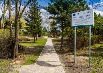 widok na ścieżkę w centrym rekreacyjnym we Wiągu, z prawej strony tablica informacyjna o inwestycji