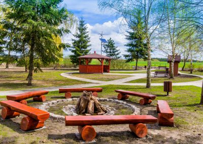 widok na miejsce na ognisko otoczone drewnianymi ławkami