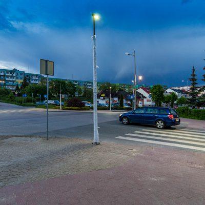 widok na skrzyżowanie ulic z oświetlonym przejściem dla pieszych
