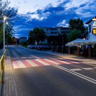 widok na ulicę z oświetlonym biało czerwonym przejściem dla pieszych