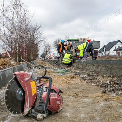 na pierwszym planie maszyna do cięcia betonu, w oddali robotnicy podczas budowy ścieżki rowerowej