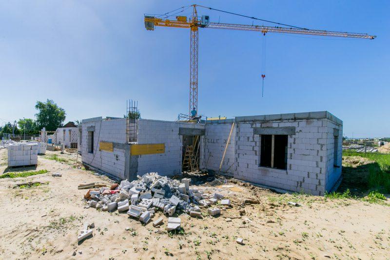 widok na budowę budynku mieszkalnego, w tle dźwig budowlany