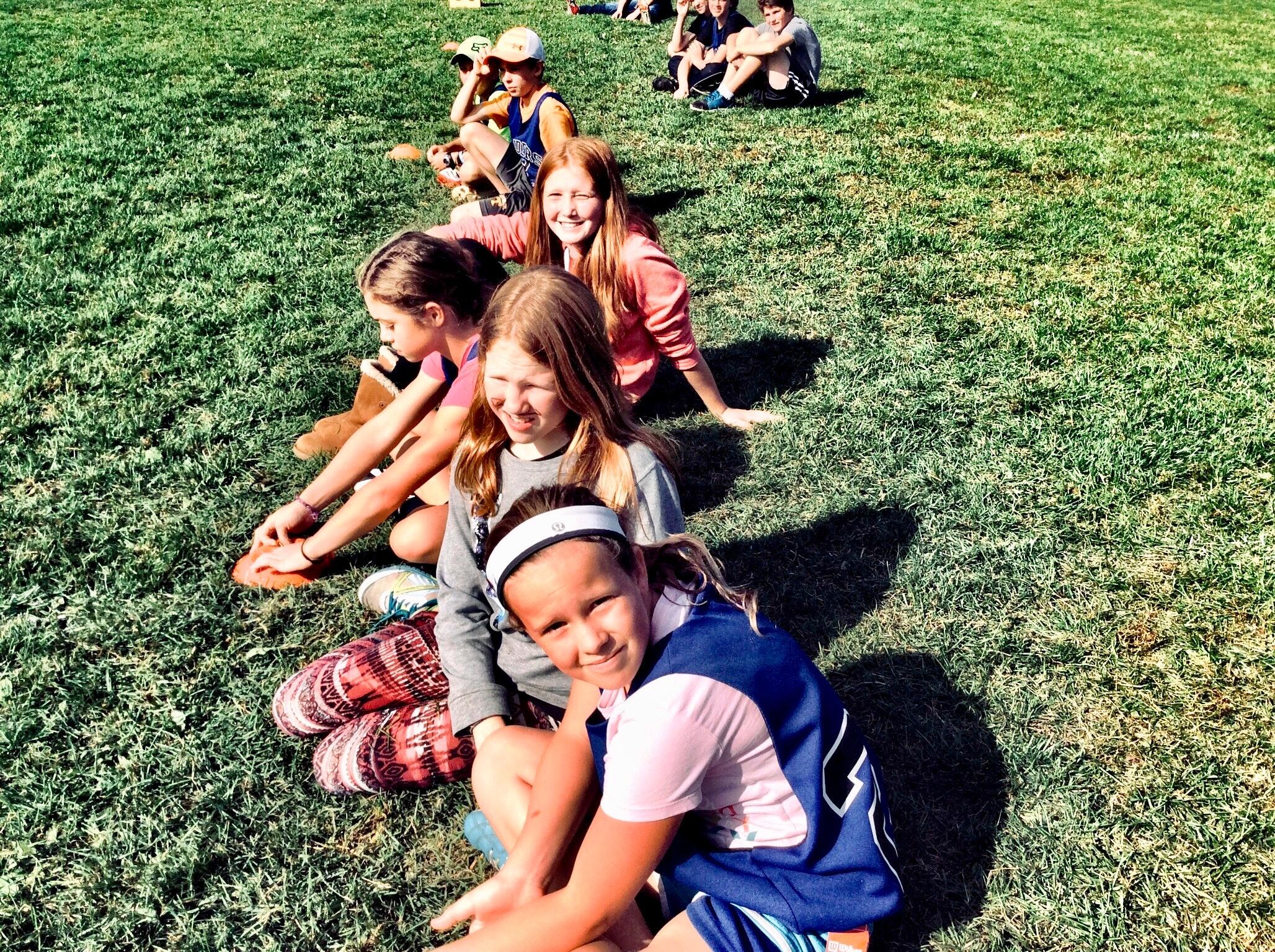 obrazek przedstawia uśmiechnięte dzieci siedzące na trawie