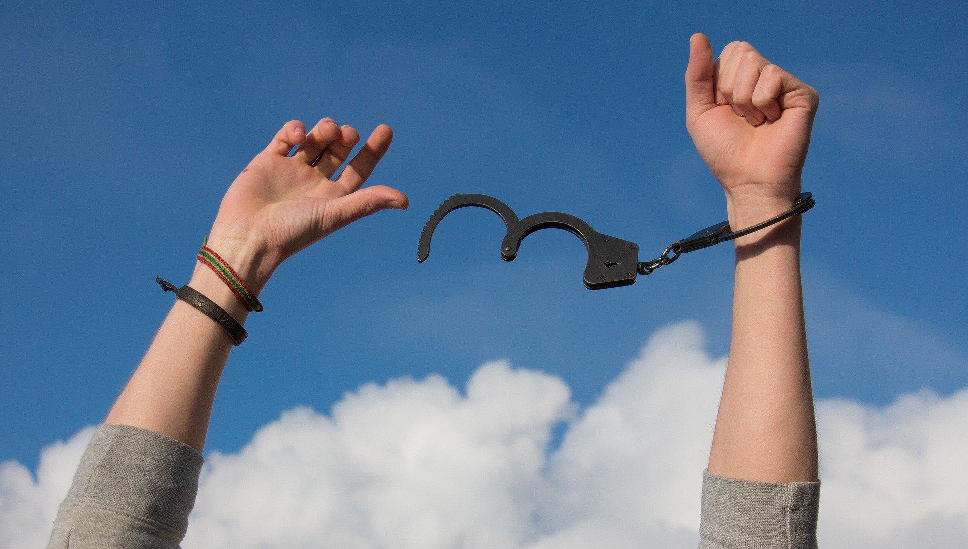 obrazek przedstawia młodego człowieka rozrywającego kajdanki