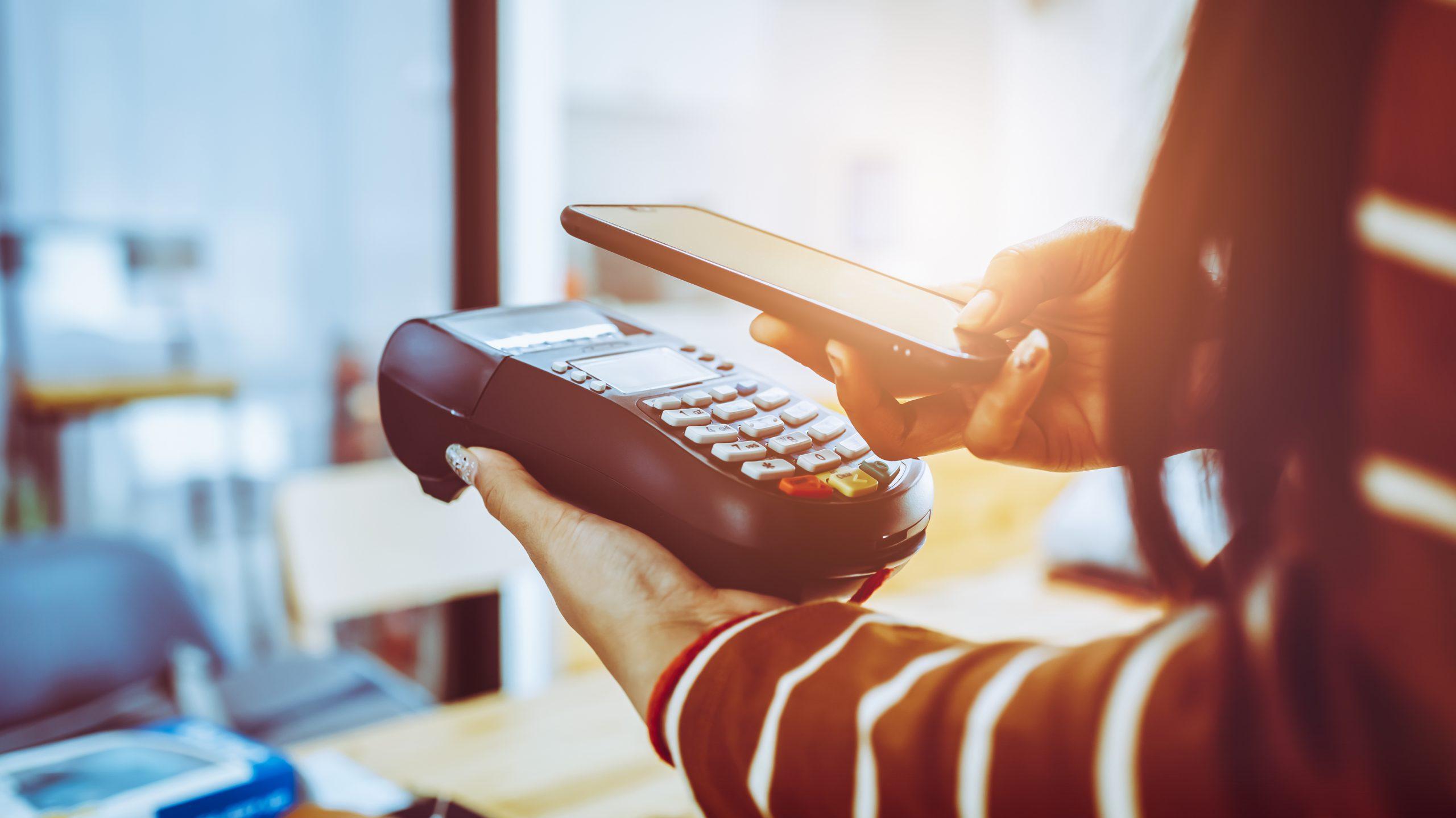 na obrazku osoba dokonująca płatności zbliżeniowej za pomocą telefonu