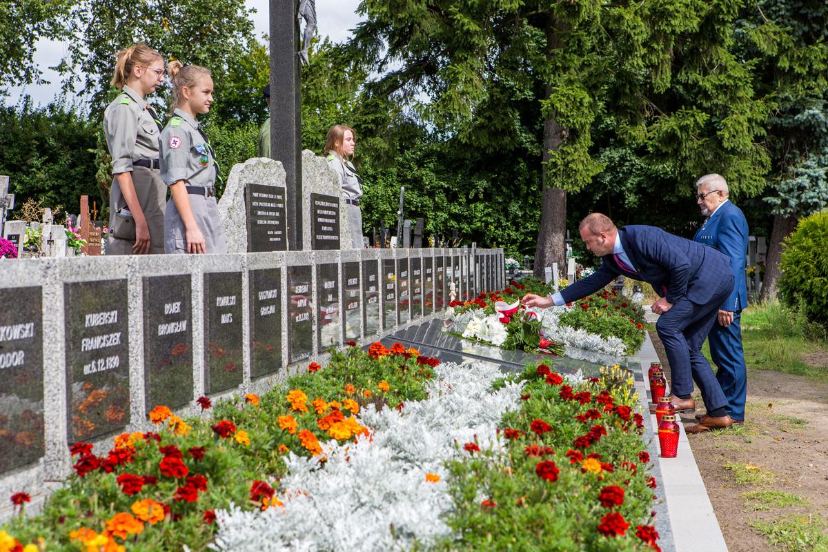 Burmistrz Krzysztof Kułakowski składa kwiaty na mogile